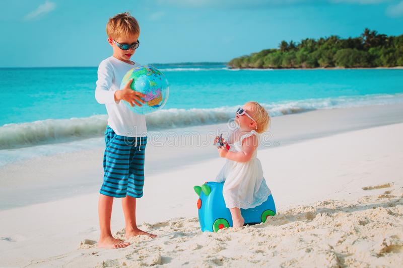 Kids play with globe and toy plane on beach, travel concept royalty free stock photos