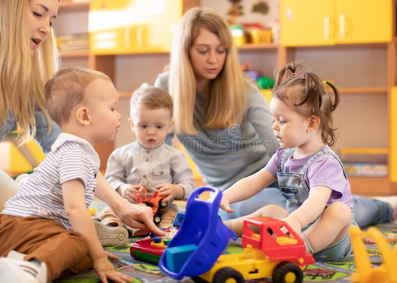 Kids play in kindergarten or daycare centre under the supervision of moms royalty free stock image