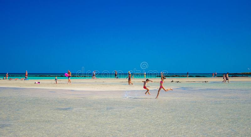 Kids play and run on the famous sandy beach of Elafonissi, Crete, Greece. Kids play and run on the famous sandy beach of Elafonissi, Crete, Greece on June 13 royalty free stock photo