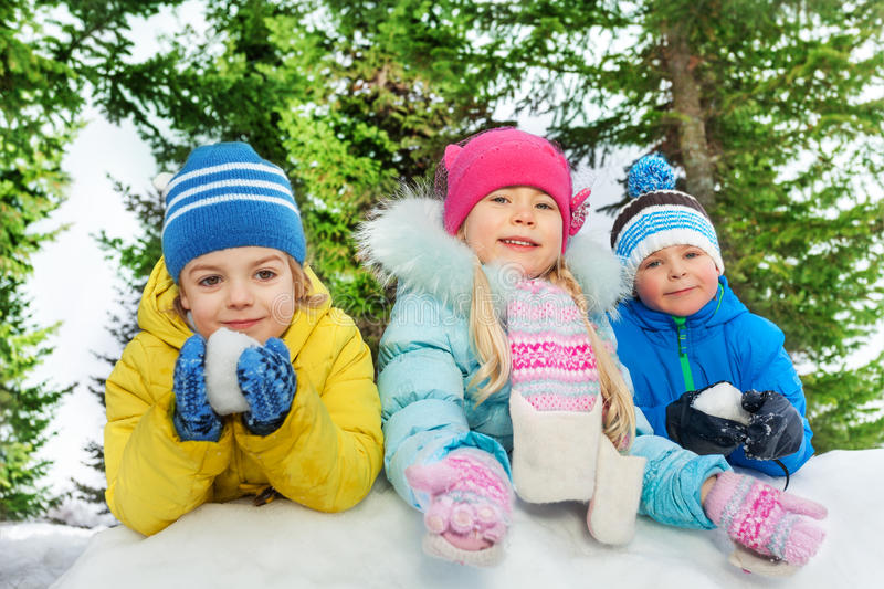 Kids play with snow together close portrait. Group of kids boys and girls play with snow outside on cold winter day royalty free stock images