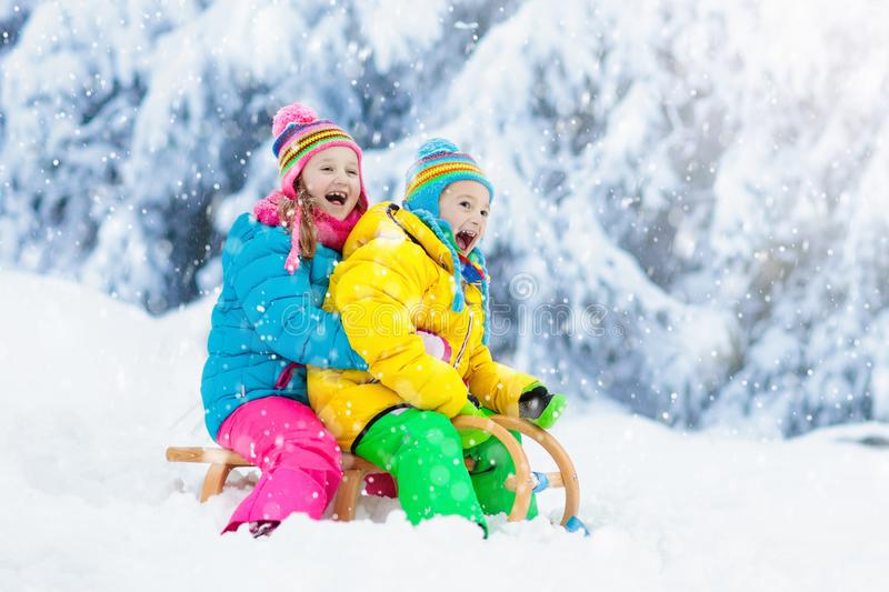 Kids play in snow. Winter sled ride for children stock photography