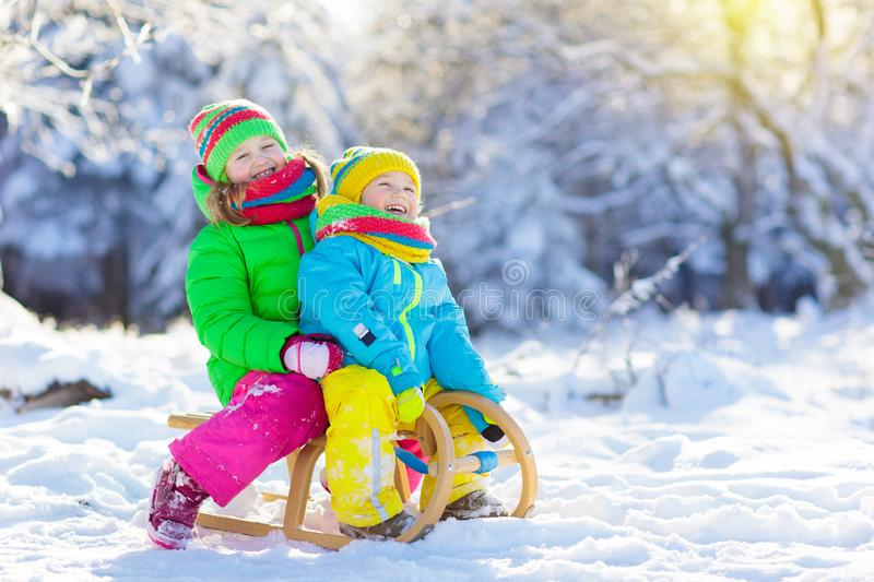 Kids play in snow. Winter sled ride for children. Little girl and boy enjoying sleigh ride. Child sledding. Toddler kid riding a sledge. Children play outdoors royalty free stock images