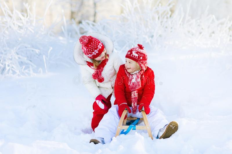 Kids play in snow. Winter sleigh ride for children. Little girl and boy enjoying sleigh ride. Child sledding. Toddler kid riding a sledge. Children play outdoors royalty free stock photo