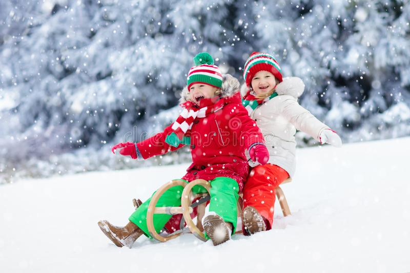 Kids play in snow. Winter sleigh ride for children. Little girl and boy enjoying sleigh ride. Child sledding. Toddler kid riding a sledge. Children play outdoors stock image