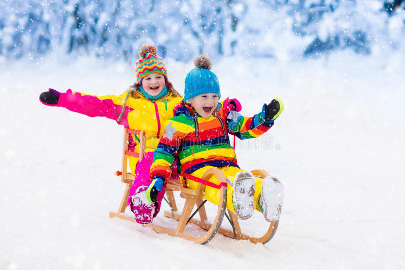 Kids play in snow. Winter sleigh ride for children. Little girl and boy enjoying sleigh ride. Child sledding. Toddler kid riding a sledge. Children play outdoors royalty free stock photos