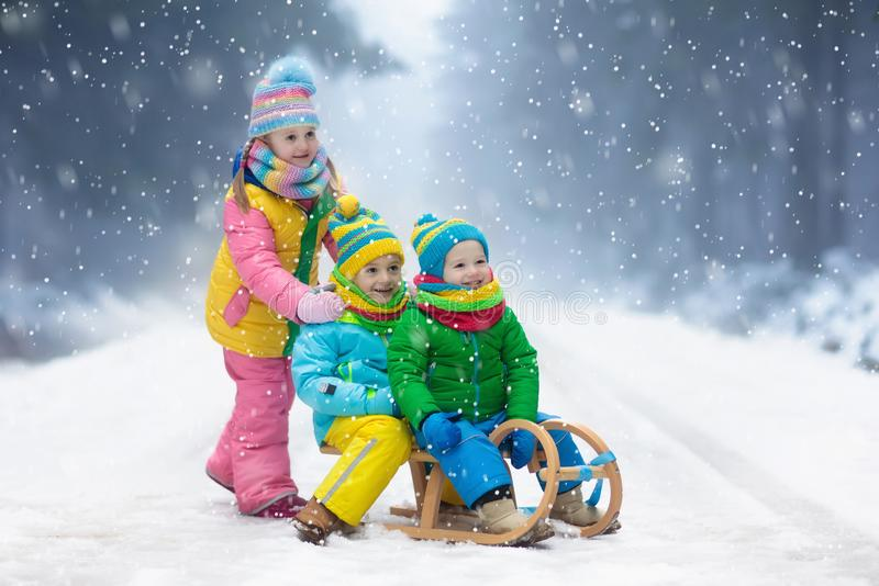 Kids play in snow. Winter sleigh ride for children. Little girl and boy enjoying sleigh ride. Child sledding. Toddler kid riding a sledge. Children play outdoors royalty free stock image