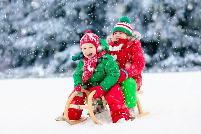 Kids play in snow. Winter sleigh ride for children. Little girl and boy enjoying sleigh ride. Child sledding. Toddler kid riding a sledge. Children play outdoors stock photography