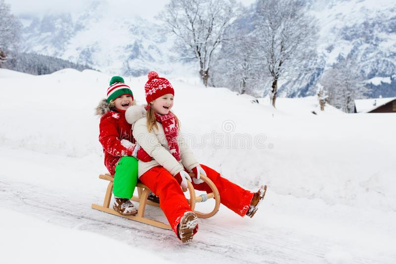 Kids play in snow. Winter sleigh ride for children. Little girl and boy enjoying sleigh ride. Child sledding. Toddler kid riding a sledge. Children play outdoors royalty free stock images