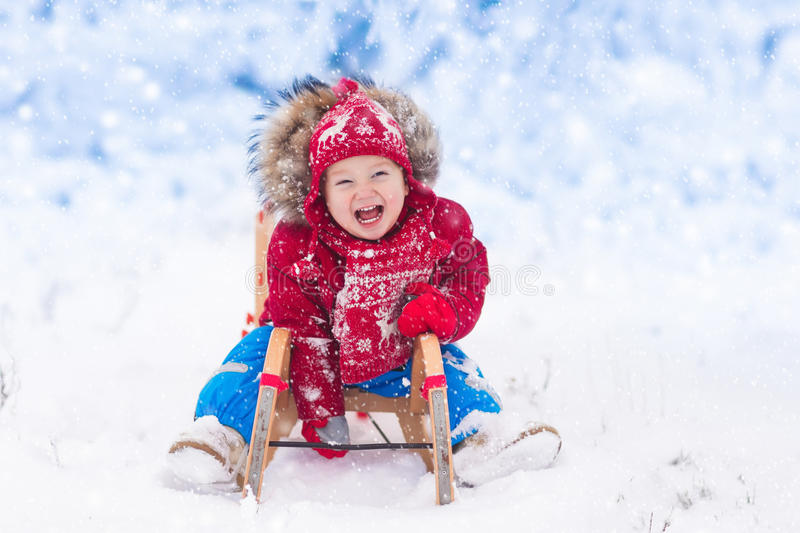 Kids play in snow. Winter sleigh ride for children. Little girl enjoying a sleigh ride. Child sledding. Toddler kid riding a sledge. Children play outdoors in royalty free stock image