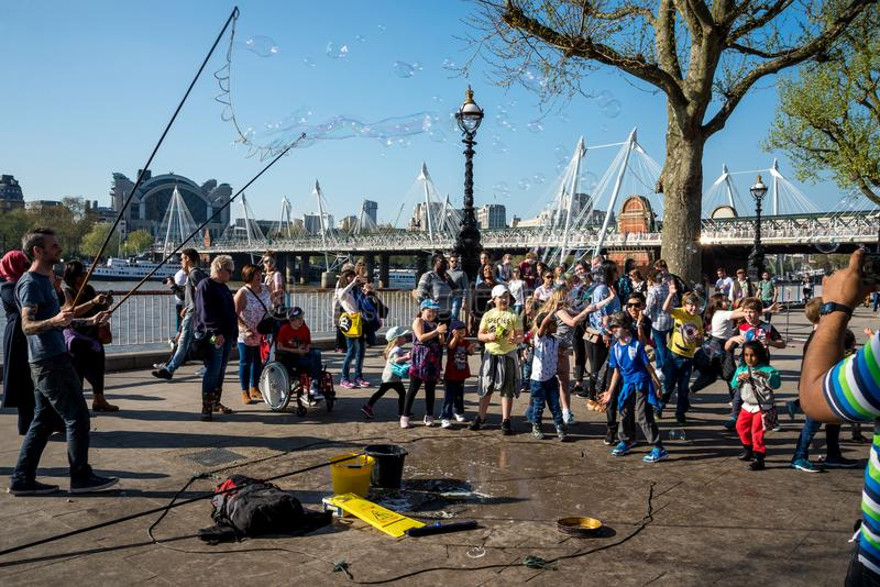 Kids play with soap bubbles during performance of one of the street artists near Jubilee gardens and London Eye Observation Wheel stock image