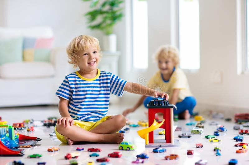 Kids play with toy cars. Children playing car toys. Kids play with toy cars in white room. Little boy playing with car and truck toys. Vehicle and transportation stock photos
