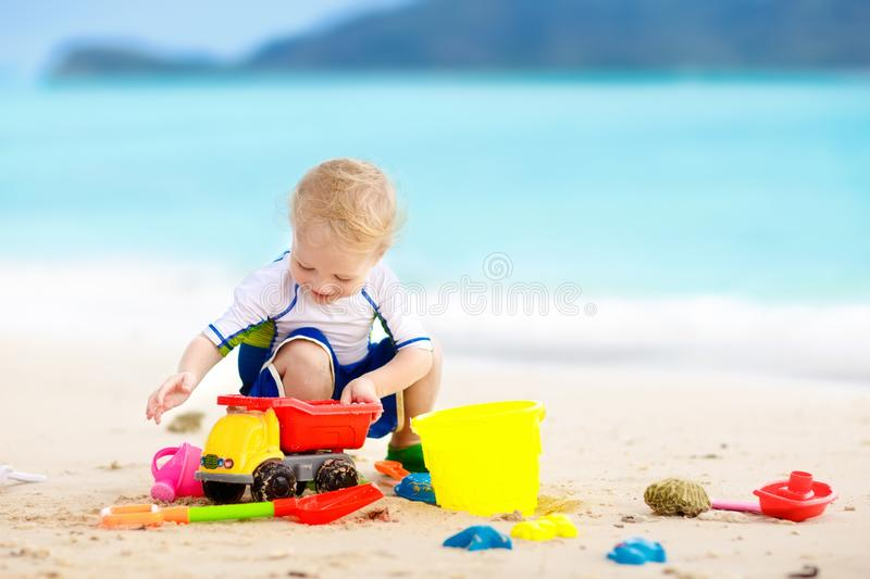 Kids play on tropical beach. Sand and water toy. Child playing on tropical beach. Little girl digging sand at sea shore. Family summer vacation. Kids play with royalty free stock images