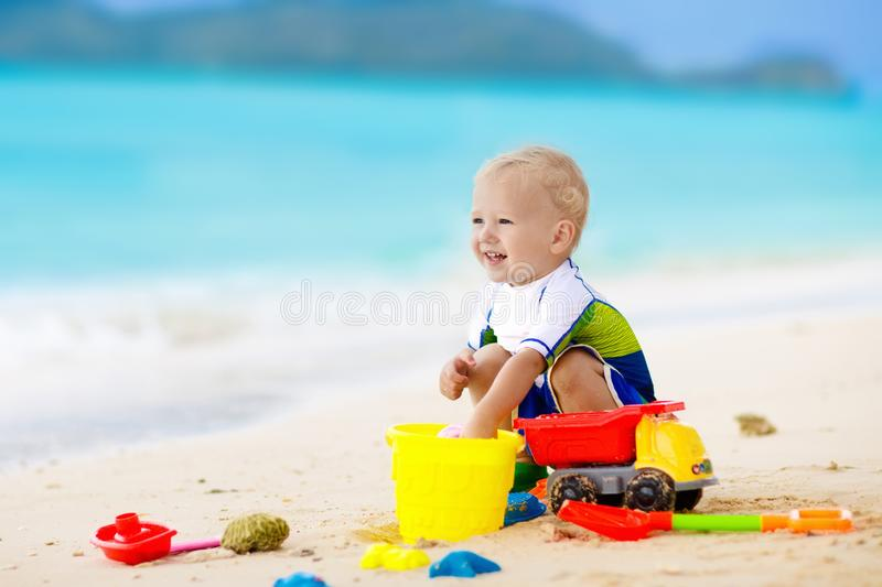 Kids play on tropical beach. Sand and water toy. Child playing on tropical beach. Little girl digging sand at sea shore. Family summer vacation. Kids play with stock photo