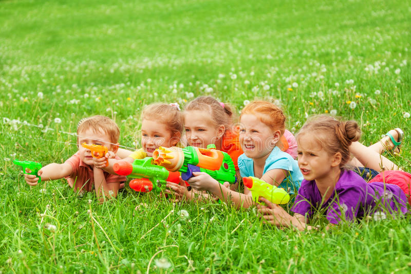 Kids play with water guns laying on a meadow royalty free stock images