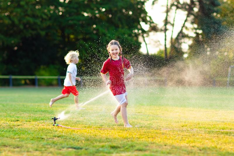 Kids play with water. Child with garden sprinkler royalty free stock images