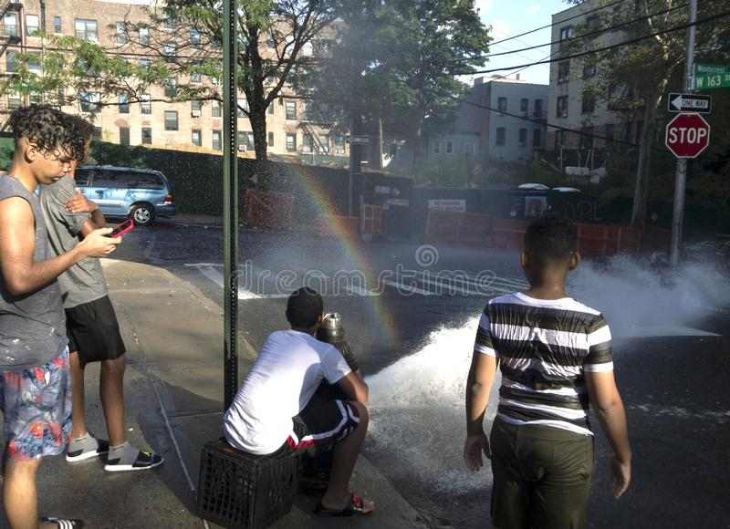 Kids play with water from open hydrand in summer. BRONX, NEW YORK/USA - July 20, 2019: Kids play with water from open fire pump in hot summer stock photos