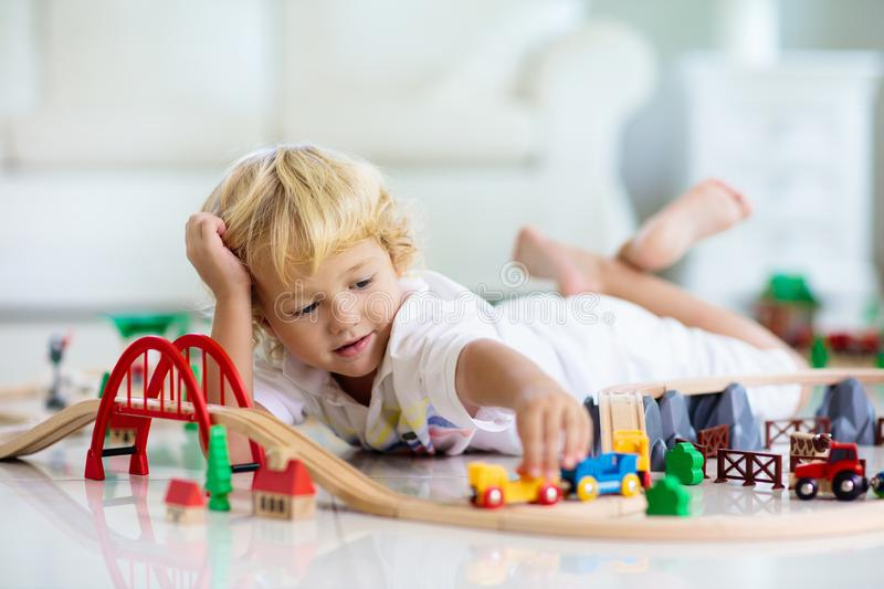 Kids play wooden railway. Child with toy train stock photos