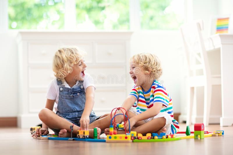 Kids play wooden railway. Child with toy train stock photo