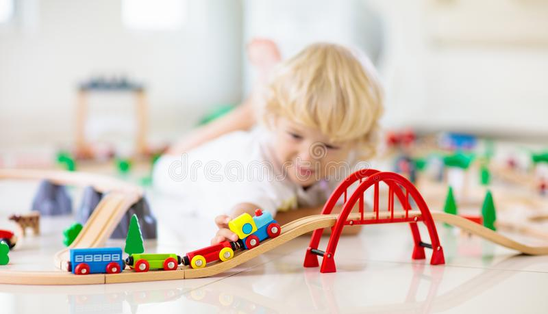 Kids play wooden railway. Child with toy train royalty free stock photo