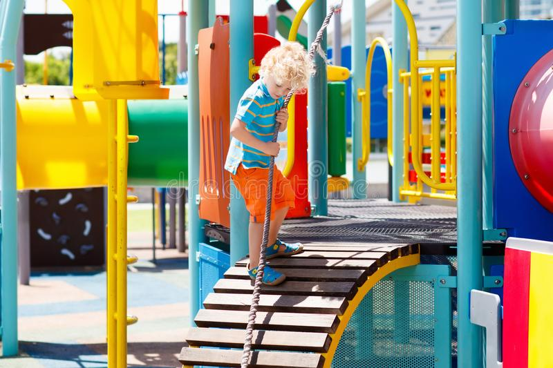 Kids on playground. Children play in summer park. Kids climbing and sliding on outdoor playground. Children play in sunny summer park. Activity and amusement royalty free stock image