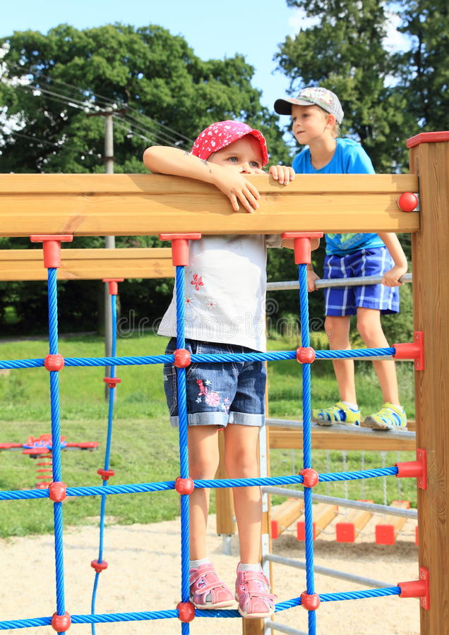 Kids on playground. Little kids on playground - girl in blue clothes with red cap with white dots standing on rope net and boy behind her exercising on hayrack royalty free stock photos