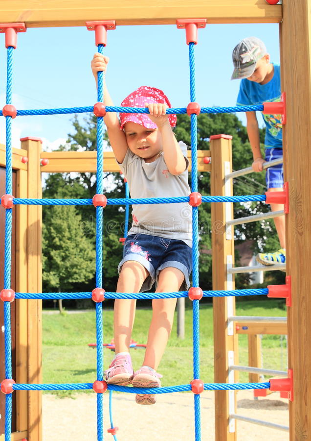 Kids on playground. Little kids on playground - girl in blue clothes with red cap with white dots standing on rope net and boy behind her exercising on hayrack stock images