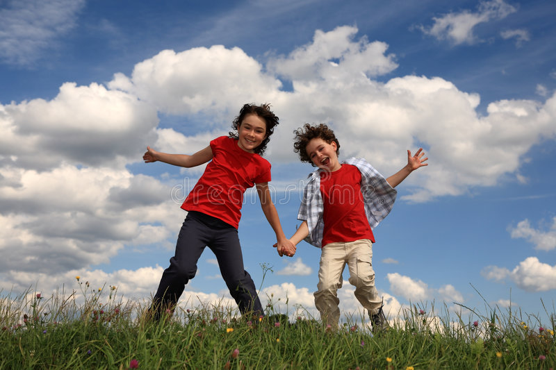 Kids playing. Kids running on green meadow royalty free stock images