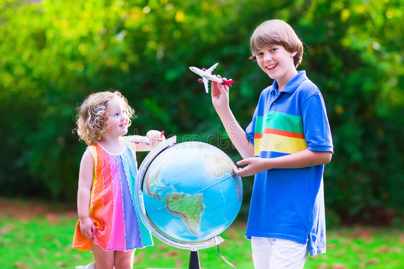 Kids playing with airplanes and globe royalty free stock photography