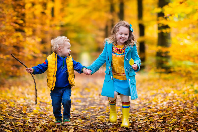 Kids playing in autumn park. Happy children playing in beautiful autumn park on cold sunny fall day. Kids in warm jackets play with golden leaves stock photos