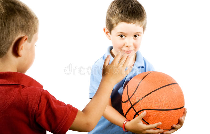Kids playing Basketball. Stock photo of boys playing basketball, isolated on white royalty free stock images
