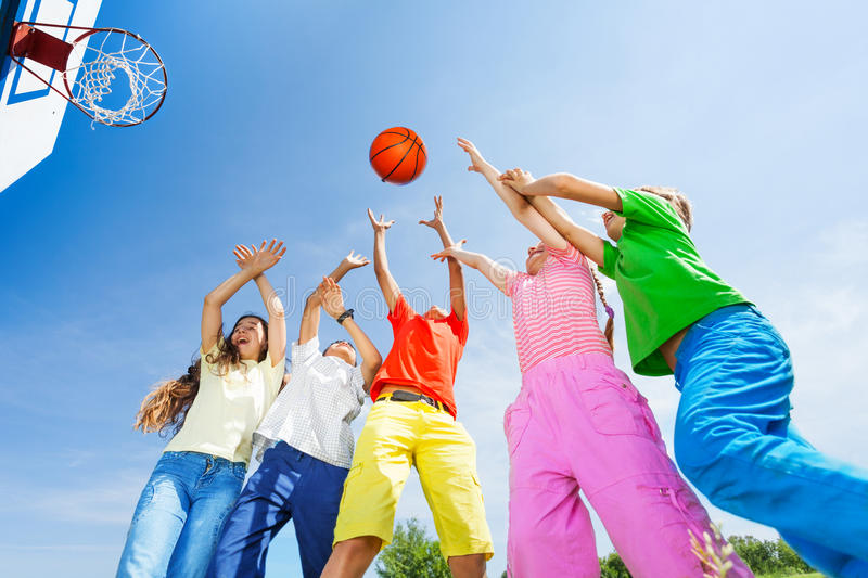 Kids playing basketball with a ball up in sky. Kids playing basketball together with a ball up in sky, view from bottom stock photo