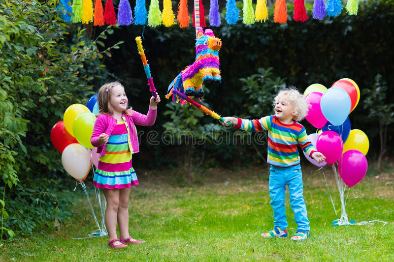 Kids playing with birthday pinata. Kids birthday party. Group of children hitting pinata and playing with balloons. Family and friends celebrating birthday royalty free stock photo