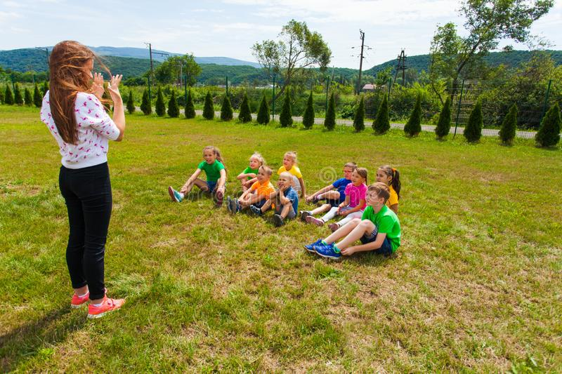 Kids playing charades outdoors in the summer camp. Group of children of different age playing charades with their teen-leader outdoors in the summer camp royalty free stock photography