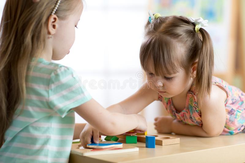 Kids playing with colorful block toys. Two children girls at home or daycare center. Educational child toys for stock image