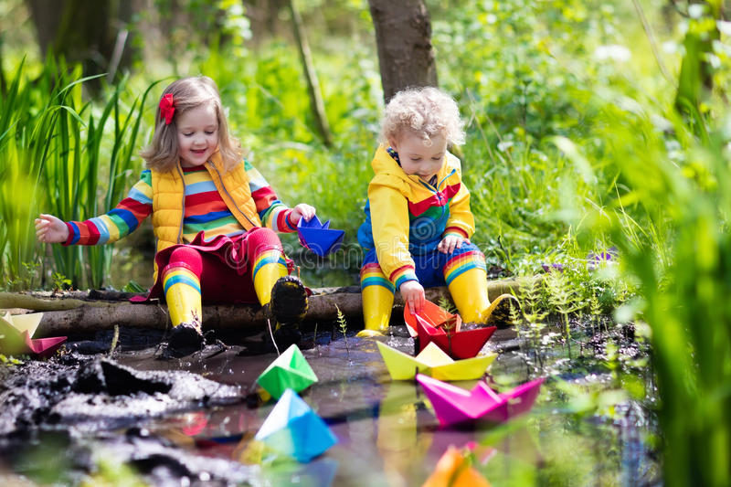 Kinder Garden: Kids Playing With Colorful Paper Boats In A Park Stock
