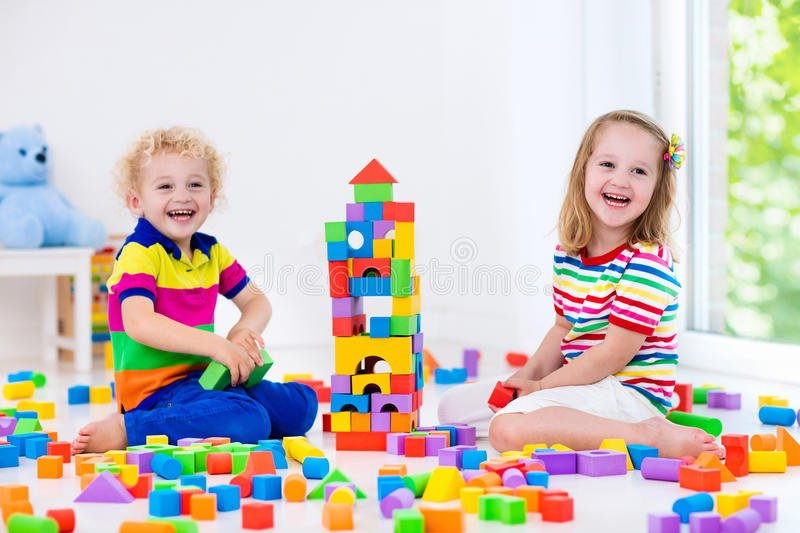 Kids playing with colorful toy blocks. Happy preschool age children play with colorful plastic toy blocks. Creative kindergarten kids build a block tower royalty free stock image
