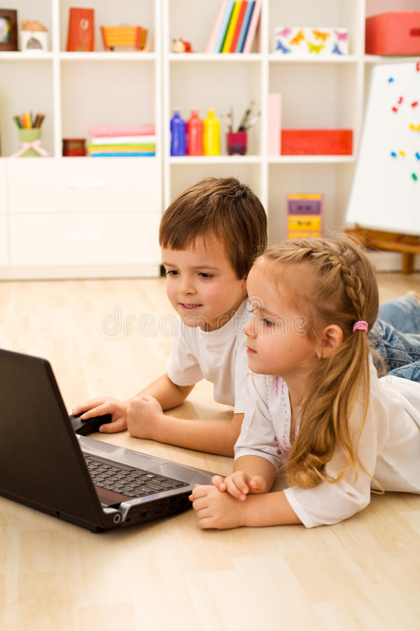 Kids playing computer game on laptop stock photography