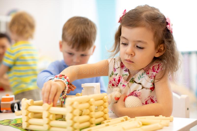 Kids playing in kindergarten. Children building toy house with plastic blocks sitting together by the table royalty free stock image