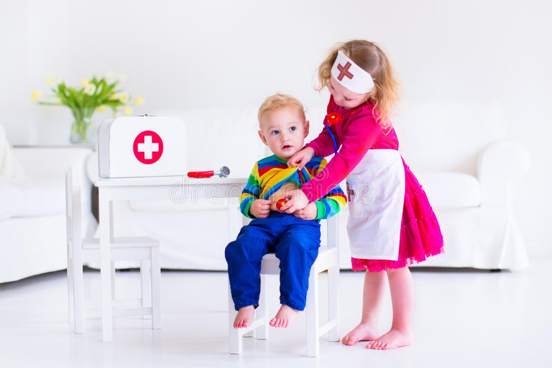 Kids playing doctor. Two happy children, cute toddler girl and adorable baby boy, brother and sister, playing doctor and hospital using stethoscope toy and royalty free stock photo