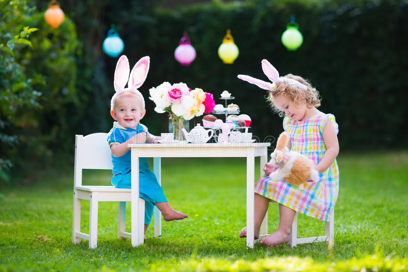 Kids playing Easter tea party with toys stock image