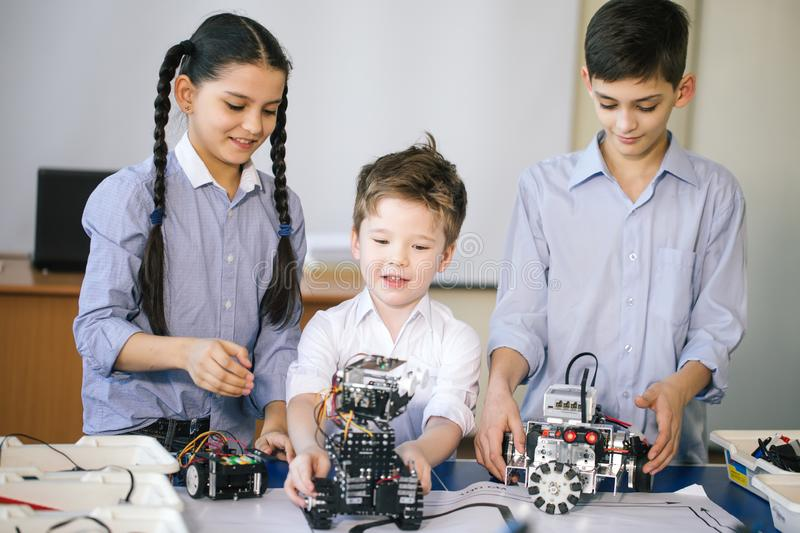 Kids playing with electrical robot while visiting robotics exhibition. Modern . Group of caucasian kids having fun participating in the competition race of robot stock photo
