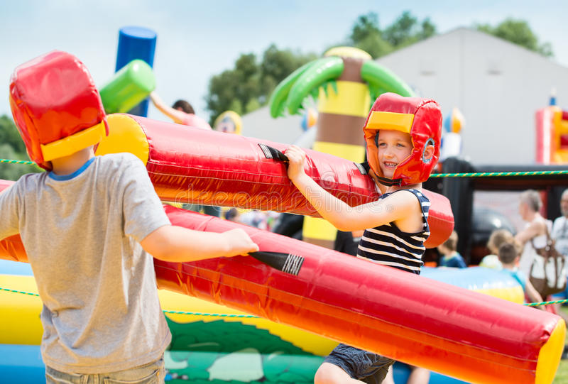 Kids playing - fighting. In colorful playground royalty free stock photos