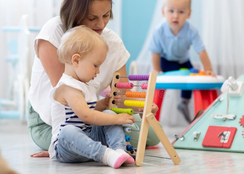 Kids playing on floor with educational toys in kindergarten. Children have fun in nursery or daycare. Babies with royalty free stock photo
