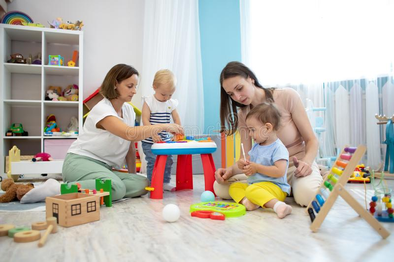 Kids playing on floor with educational toys. Toys for preschool and kindergarten. Children in nursery or daycare. Babies stock photos