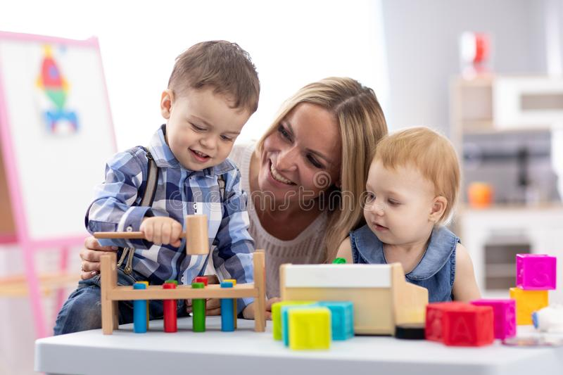 Kids playing with mother at table with educational toys. Toys for preschool and kindergarten. Children in nursery or royalty free stock photos