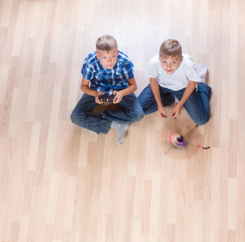 Kids playing with flying helicopter model at home using remote control stock photo