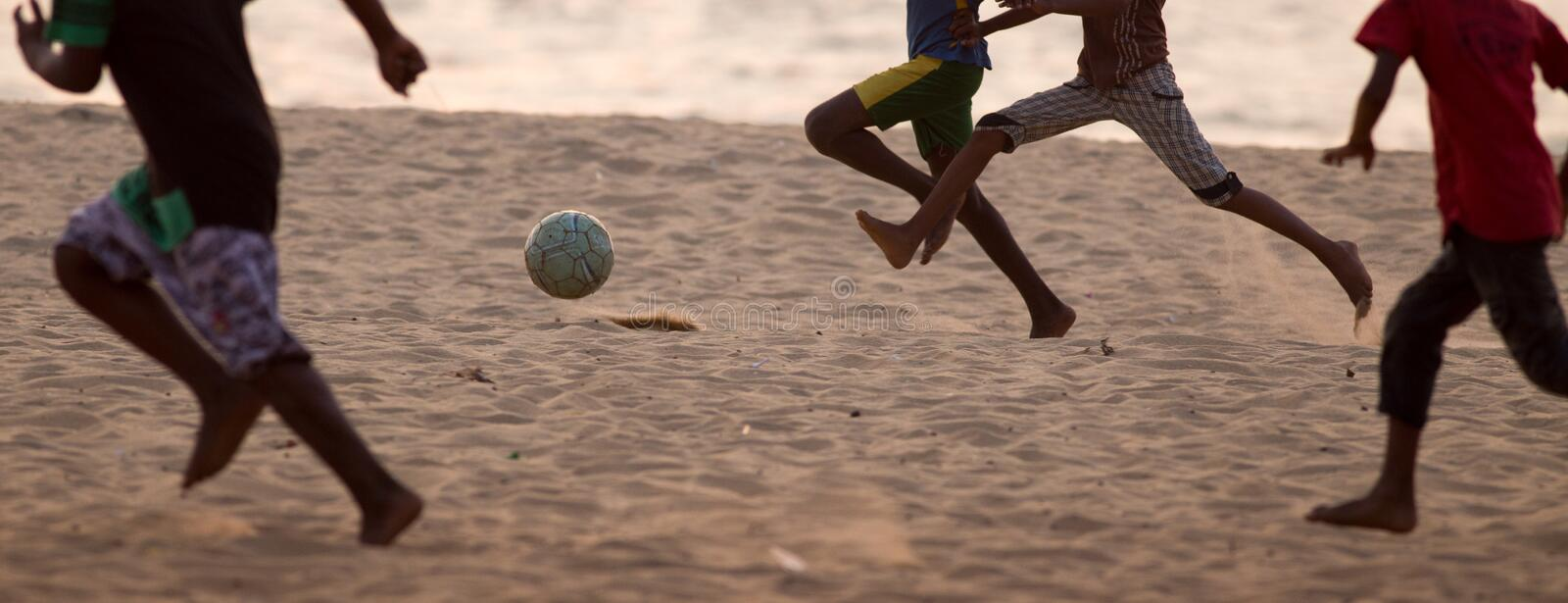 Kids playing football barefoot on sand royalty free stock images