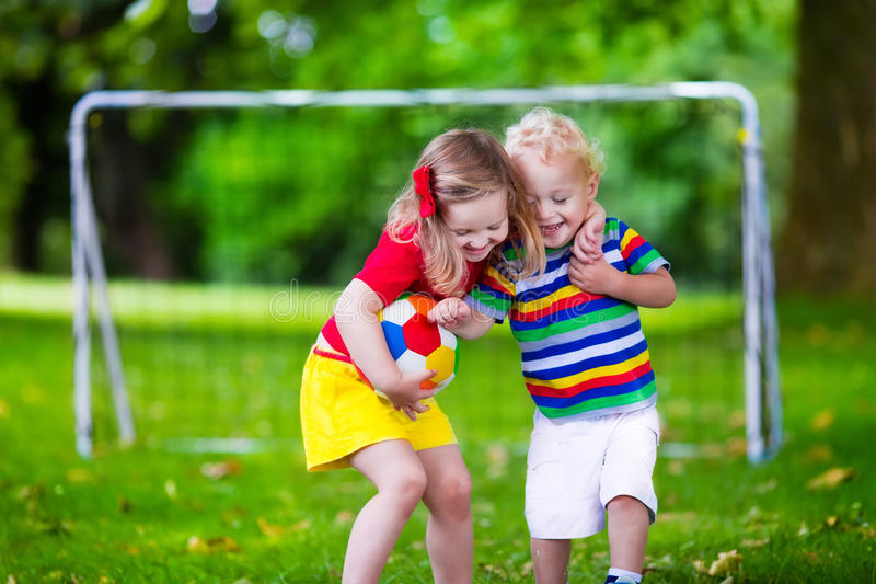 Kids playing football in a park. Two happy children playing European football outdoors in school yard. Kids play soccer. Active sport for preschool child. Ball royalty free stock photos