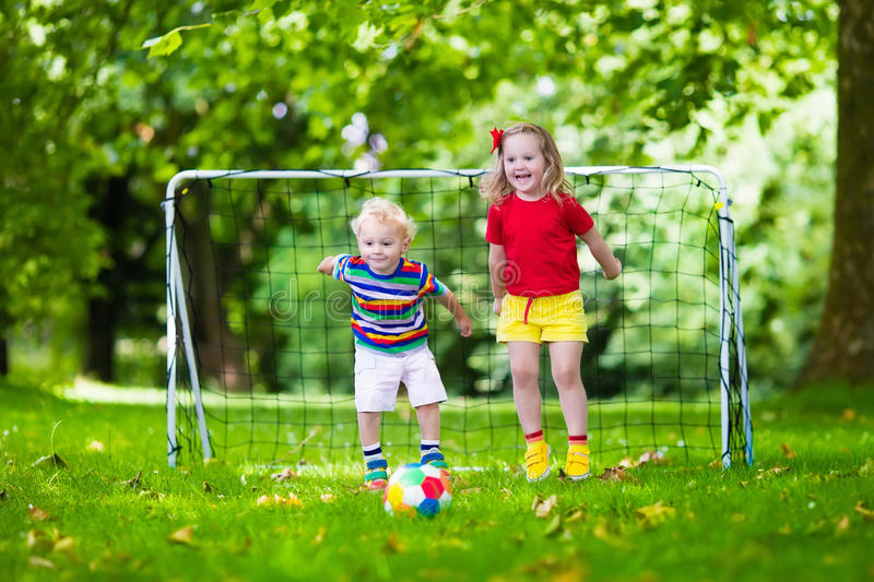 Kids playing football in school yard. Two happy children playing European football outdoors in school yard. Kids play soccer. Active sport for preschool child royalty free stock photo
