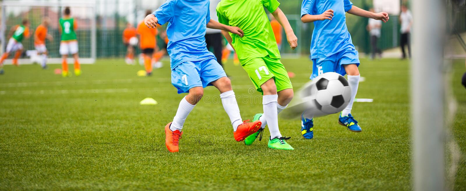 Kids playing football together; Children playing soccer football game outdoor stock image